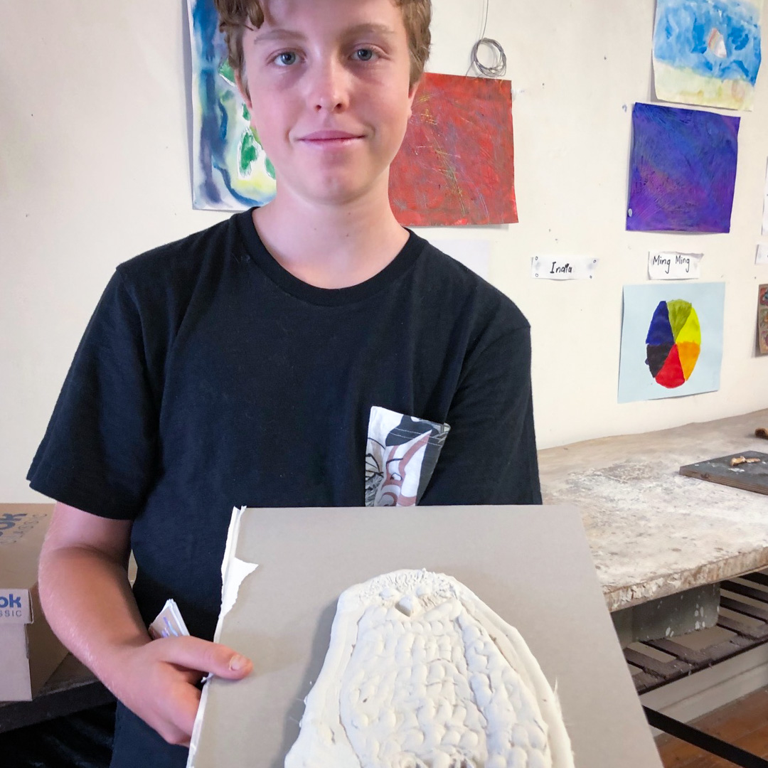 Class Artwork – Student with bas-relief animal sculpture – click to view class details