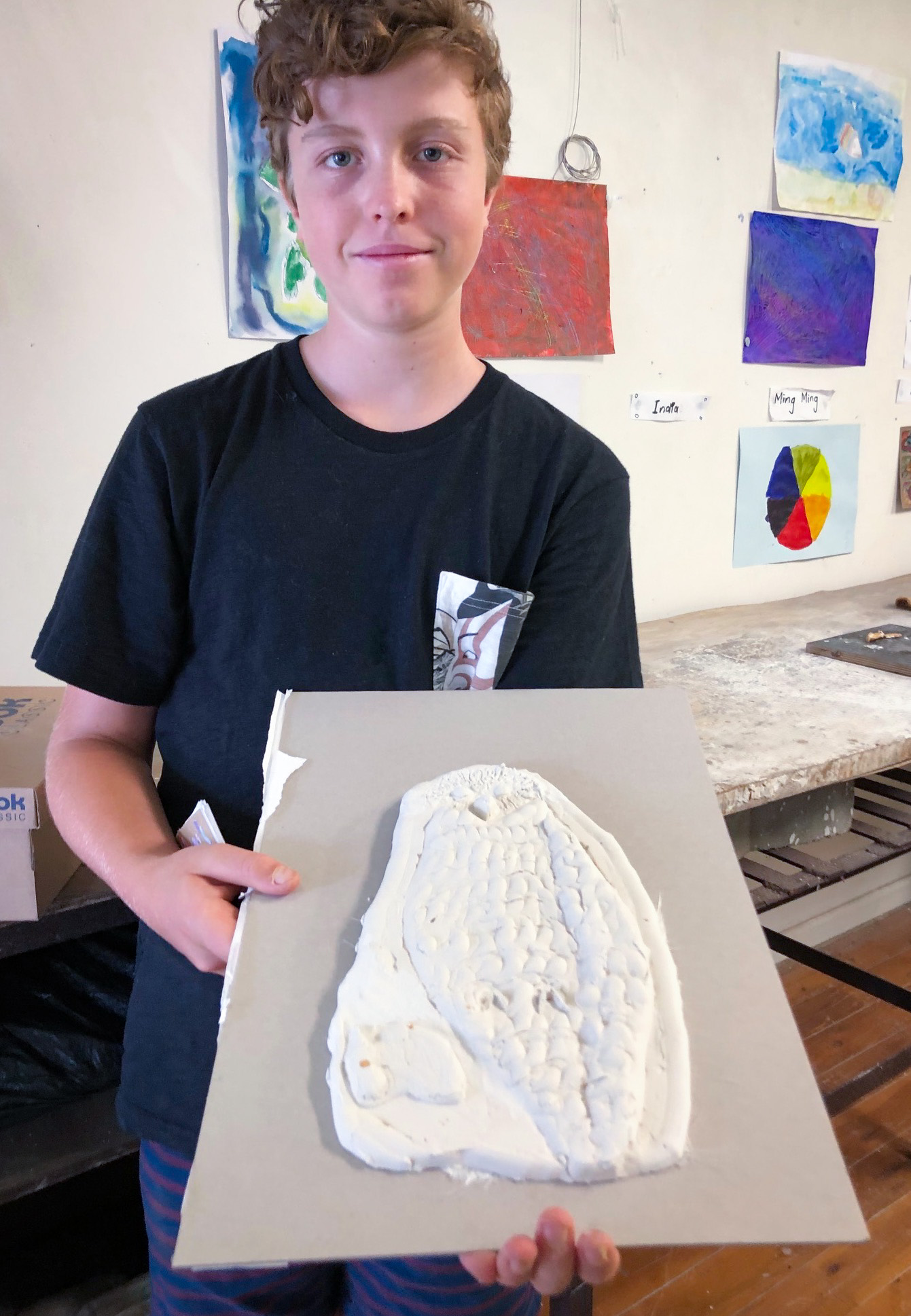 Class Artwork – Student with bas-relief animal sculpture